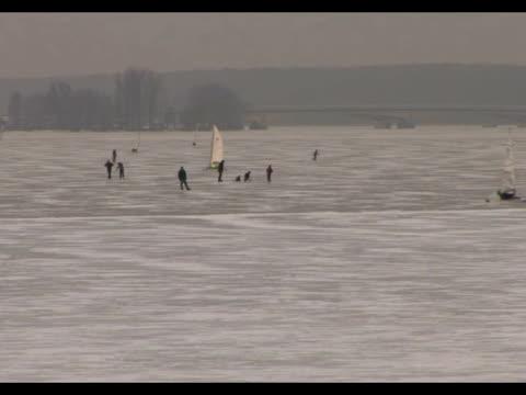 mientras se mantiene la ola de frio que golpea europa, polacos entusiastas de los deportes de hielo organizan corridas sobre gruesas capas de hielo,... - hielo video stock e b–roll