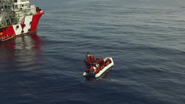 a migrant boat is found by a rescue ship off the italian coast in 2017 panning drone shot - flytväst bildbanksvideor och videomaterial från bakom kulisserna