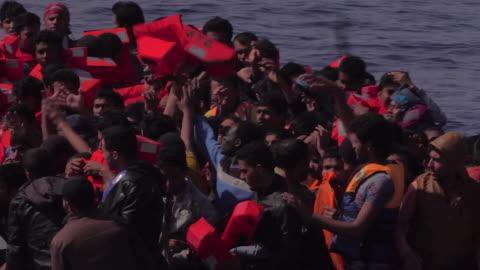 vídeos y material grabado en eventos de stock de migrant boat is found off the italian coast 2017, migrants handed lifejackets and then board a rescue ship - equipo de seguridad