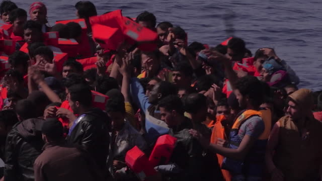 migrant boat is found off the italian coast 2017, migrants handed lifejackets and then board a rescue ship - crisis stock videos & royalty-free footage