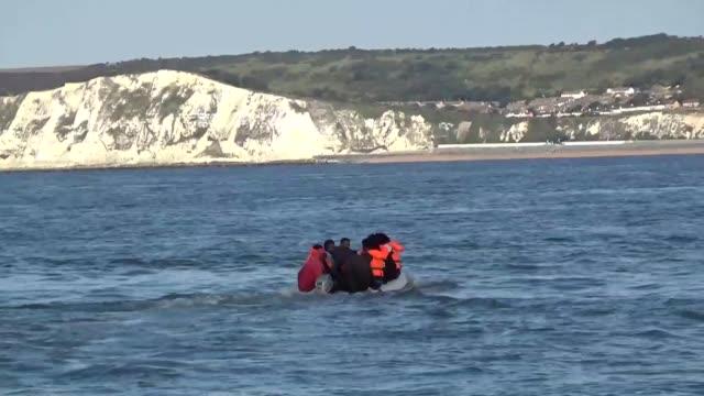 migrant channel crossings: migrants in inflatable dinghy gvs; england: dover: english channel: ext / at sea refugees in inflatable dinghy - chatting... - kent england bildbanksvideor och videomaterial från bakom kulisserna