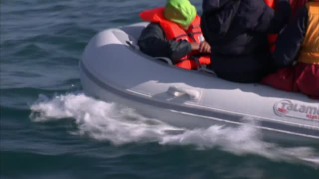 nine migrants cross from calais to dover english various shots of dinghy carrying migrants along at sea migrants on dinghy shouting to reporter on... - sea channel stock videos and b-roll footage