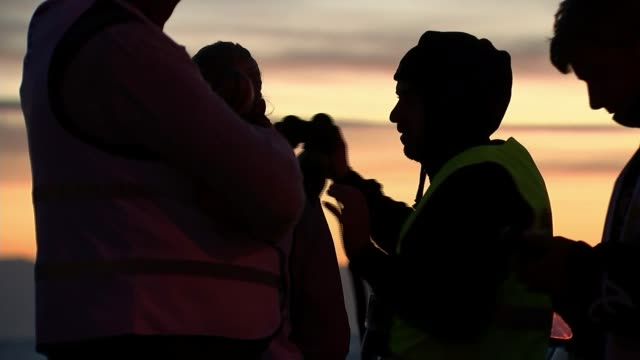vídeos de stock, filmes e b-roll de refugee situation on lesbos / royal navy ship to patrol aegean sea greece lesbos ext various shots aid workers on beach at sunrise rubber dinghy... - migrant worker