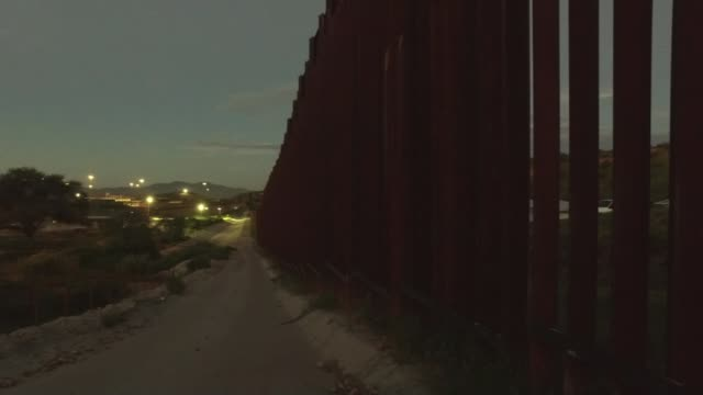 migrant detention camp for children condemned as 'cruel'; usa: texas: ext / dusk fence pathway alongside border fence 'border patrol' cabin spiked... - spiked stock videos & royalty-free footage