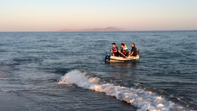 Migrant families arrive in an inflatable dinghy on the beach at sunrise on August 30 2015 in Kos Greece Migrants from many parts of the Middle East...