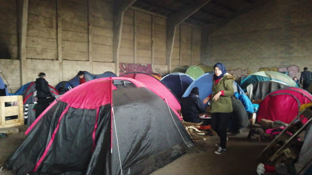 migrant families from iraq and iran camp in a derelict industrial building on february 01 2020 in dunkirk france migrants are still hopeful of... - flüchtlingslager stock-videos und b-roll-filmmaterial