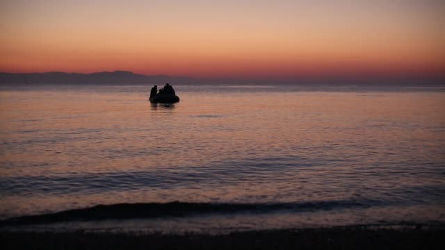 Migrant families from Syria arrive in an inflatable dinghy on the beach at sunrise on the island of Kos after crossing a three mile stretch of the...