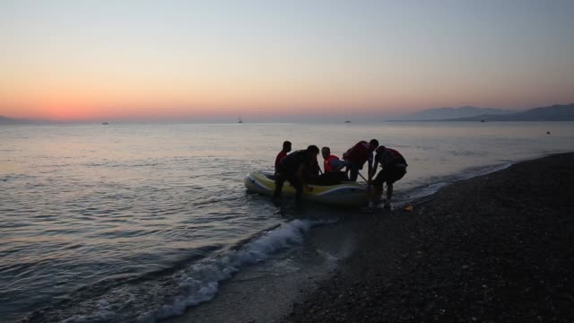migrant families from syria arrive in an inflatable dinghy on the beach at sunrise on the island of kos after crossing a three mile stretch of the... - flüchtling stock-videos und b-roll-filmmaterial