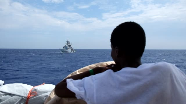 a migrant onboard the rescue vessel aquarius observes a navy ship patrolling the mediterranean sea on september 11 2016 he was rescued hours before... - questioni sociali video stock e b–roll