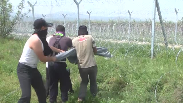 migrants and refugees remove barbed wire along the border during a protest to call for the reopening of the greekmacedonian border while some... - makeshift stock videos and b-roll footage
