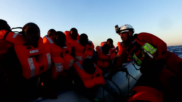 vídeos de stock e filmes b-roll de migrants are helped off a small rubber boat by crew members from the migrant offshore aid station phoenix vessel on june 10, 2017 off lampedusa,... - resgate
