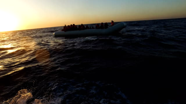migrants are helped off a small rubber boat by crew members from the migrant offshore aid station phoenix vessel on june 10 2017 off lampedusa italy... - flüchtling stock-videos und b-roll-filmmaterial