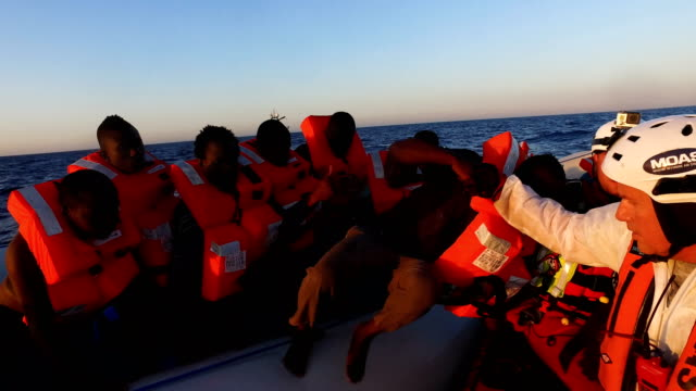 stockvideo's en b-roll-footage met migrants are helped off a small rubber boat by crew members from the migrant offshore aid station phoenix vessel on june 10 2017 off lampedusa italy... - vluchteling ontheemden