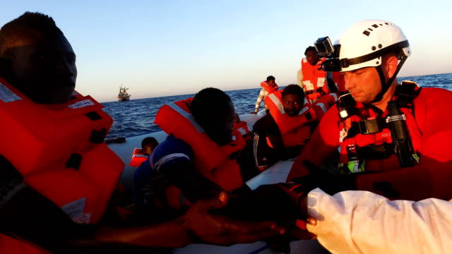 migrants are helped off a small rubber boat by crew members from the migrant offshore aid station phoenix vessel on june 10 2017 off lampedusa italy... - 難民点の映像素材/bロール