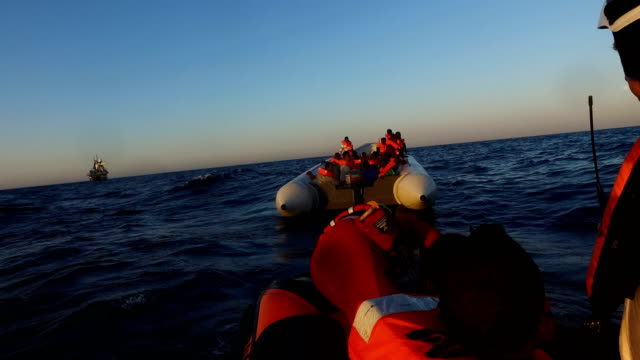 stockvideo's en b-roll-footage met migrants are helped off a small rubber boat by crew members from the migrant offshore aid station phoenix vessel on june 10, 2017 off lampedusa,... - red sea