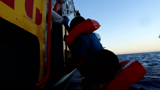 migrants are helped onto the migrant offshore aid station phoenix vessel on june 10 2017 off lampedusa italy an estimated 230000 refugees and... - befreiung stock-videos und b-roll-filmmaterial
