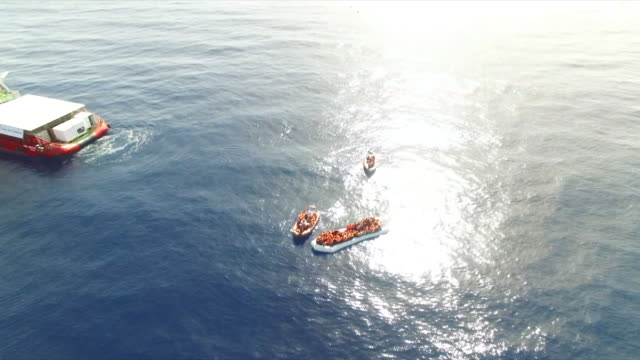 Migrants are transferred into a dingy before boarding a rescue ship off the Italian coast in 2017