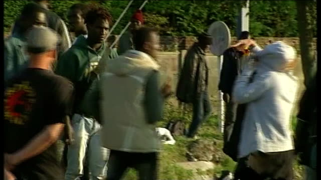 migrants clash with police in calais france calais ext east african migrants dispersing as french police car stops in road with wailing siren sot... - calais stock videos and b-roll footage