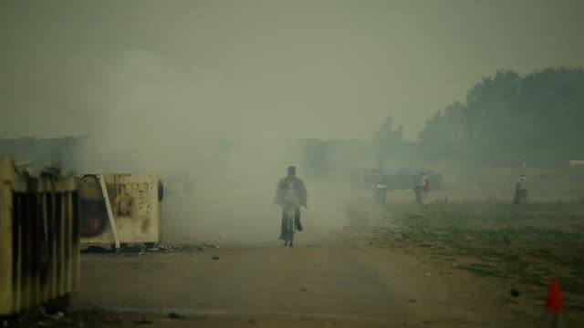 migrants cycle through smoke from a fire burning rubbish at the jungle migrant camp on september 6, 2016 in calais, france. the drop-in cafe for... - other stock videos & royalty-free footage