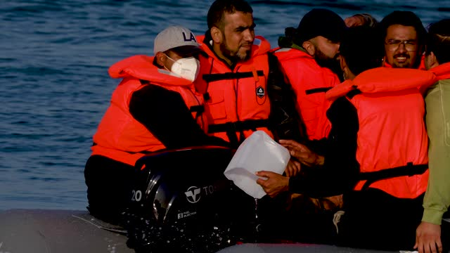 migrants empty water as the boat is to fall and taken on water as an inflatable craft carrying migrant men, women and children crosses the shipping... - males stock videos & royalty-free footage
