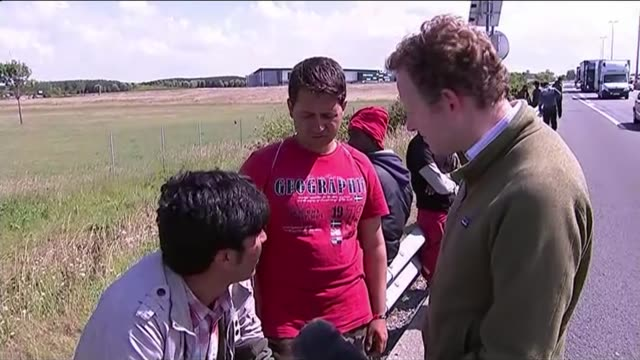 migrants exploit calais port strike reporter talking with pakistan migrants sot migrants alongside queuing lorries men climbing into back of queuing... - calais stock videos and b-roll footage