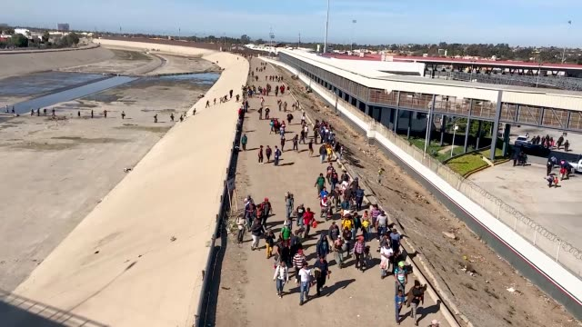 Migrants from the 'migrant caravan' cross the nearly dry Tijuana River as they make their way around a police blockade toward the El Chaparral port...