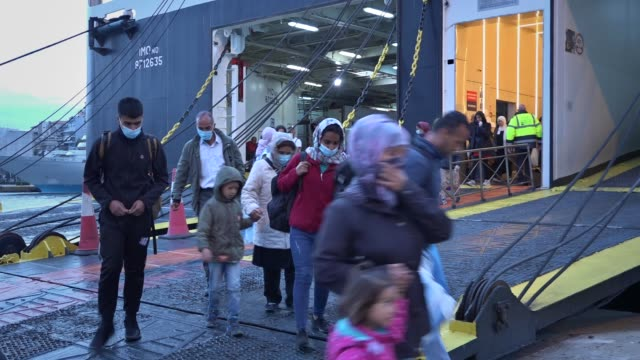 migrants from the moria camp in lesbos island wearing face masks to prevent the spread of the coronavirus, wait for a bus after their arrival at the... - refugee camp stock videos & royalty-free footage