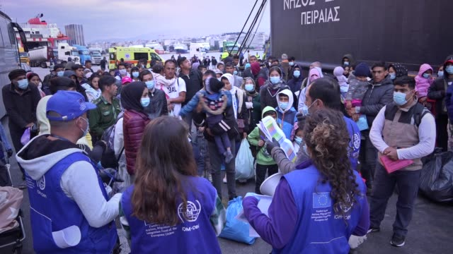 migrants from the moria camp in lesbos island wearing face masks to prevent the spread of the coronavirus wait for a bus after their arrival at the... - refugee camp stock videos & royalty-free footage