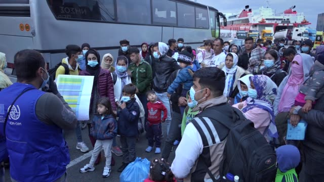 migrants from the moria camp in lesbos island wearing face masks to prevent the spread of the coronavirus, wait for a bus after their arrival at the... - greece stock videos & royalty-free footage