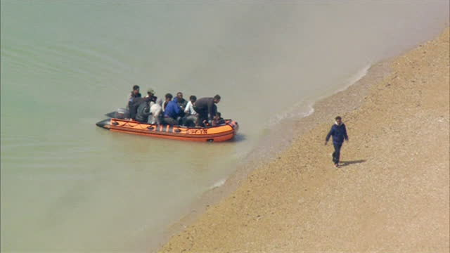 """migrants in inflatable boat arriving in dungeness, kent, after crossing the english channel from france - """"bbc news"""" stock videos & royalty-free footage"""