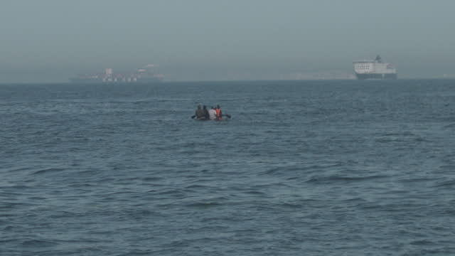 """migrants in inflatable boat using paddles to cross the english channel from france to england - """"bbc news"""" stock videos & royalty-free footage"""