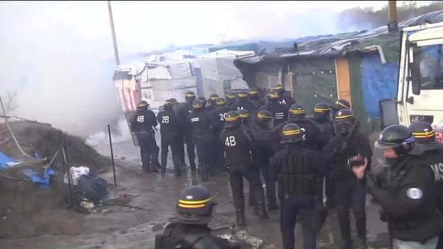 vídeos de stock e filmes b-roll de migrants look on as police officers clear part of the 'jungle' migrant camp on february 29 2016 in calais france the french authorities have begun... - crise de migrantes europeia 2015 2016