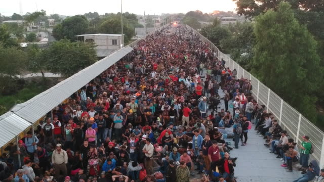 migrants mass on the bridge that connects tecun uman guatemala with ciudad hidalgo mexico on their way to united states on monday january 20 2020 - flüchtling stock-videos und b-roll-filmmaterial