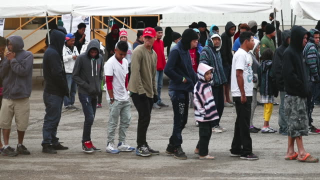 migrants most of whom are part of a recently arrived caravan are seen at a migrant hostel as they wait to apply for asylum in to the united states on... - 隊列点の映像素材/bロール
