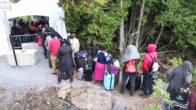 Migrants mostly Haitians fearing expulsion from the United States wait to cross the border Sunday into Canada which is experiencing a surge in asylum...