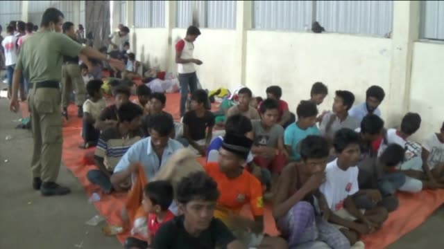 Migrants rest at temporary shelter in Langsa Aceh Indonesia on May 17 2015 Rohingya and Bangladeshi migrants wait in food queue at temporary shelter...