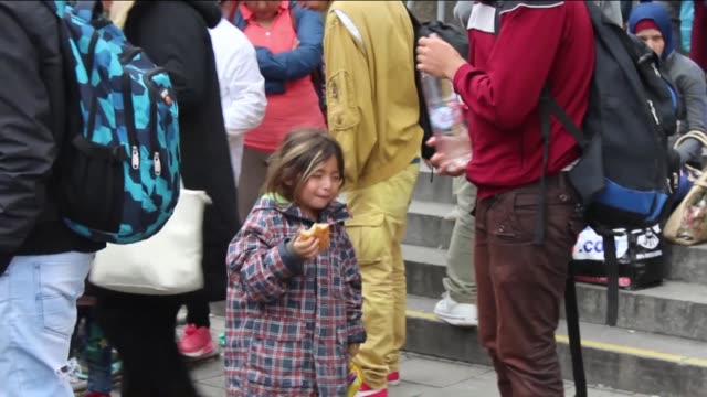 vidéos et rushes de migrants travelled by train to the main railway station 'munich hauptbahnhof' wait for a bus to reach a refugee centre on september 06, 2015 in... - 2015
