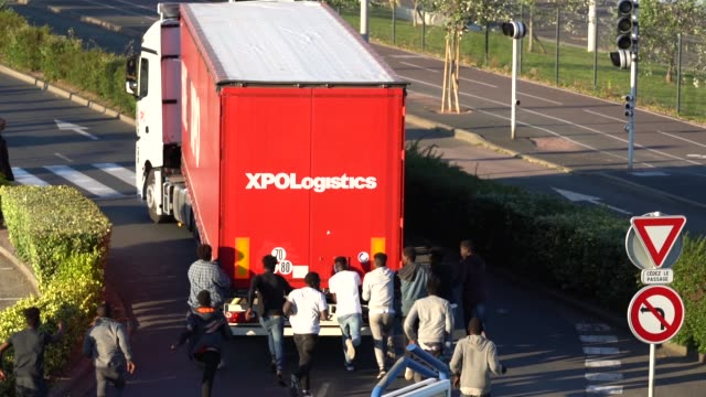 migrants try to board a truck at ouistreham ferry port in the hope of reaching the uk on september 11 2018 in ouistreham france after the clamp down... - emigration and immigration stock videos & royalty-free footage