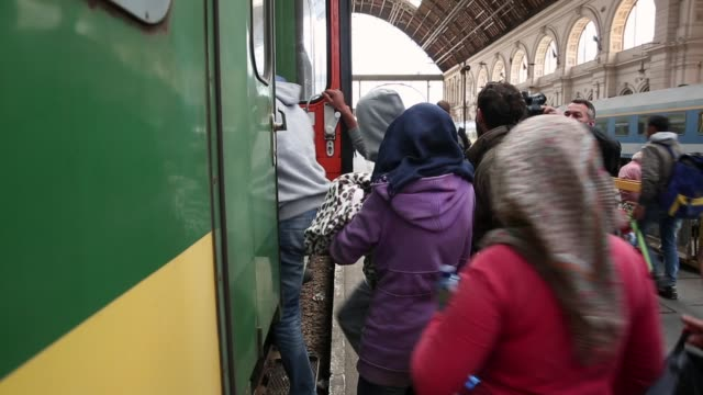 migrants wait for a to a train bound for the austrian border at the keleti railway station on september 9, 2015 in budapest, hungary. migrants in... - budapest stock-videos und b-roll-filmmaterial