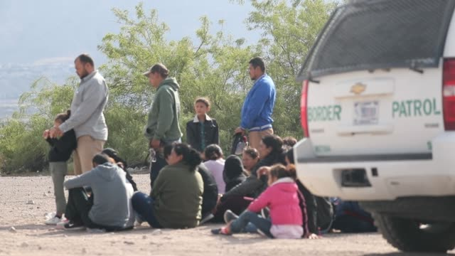 migrants wait to be processed and loaded onto a bus by border patrol agents after being detained when they crossed illegally into the united states... - border patrol stock videos & royalty-free footage