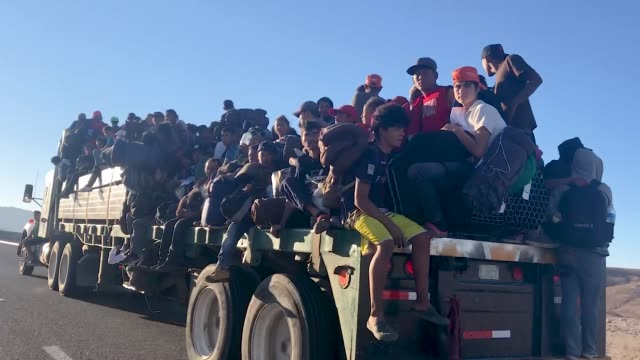 migrants who are part of the 'migrant caravan' gather on various parts of a truck while making their way to tijuana on november 20 2018 near mexicali... - tijuana stock videos & royalty-free footage