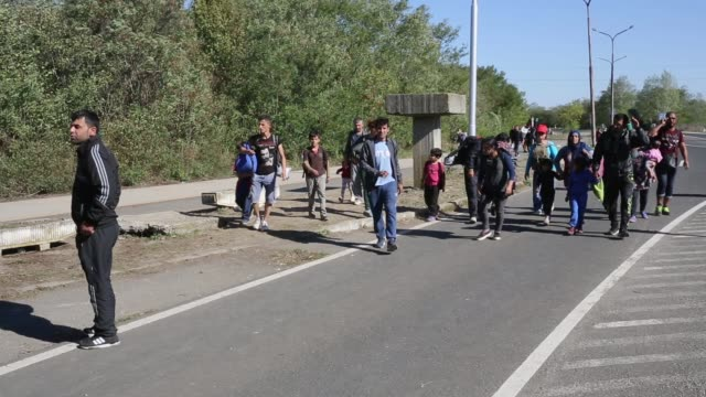 Migrants who arrived on the second train today at Hegyeshalom on the Hungarian and Austrian border clamour for food as they walk the four kilometres...