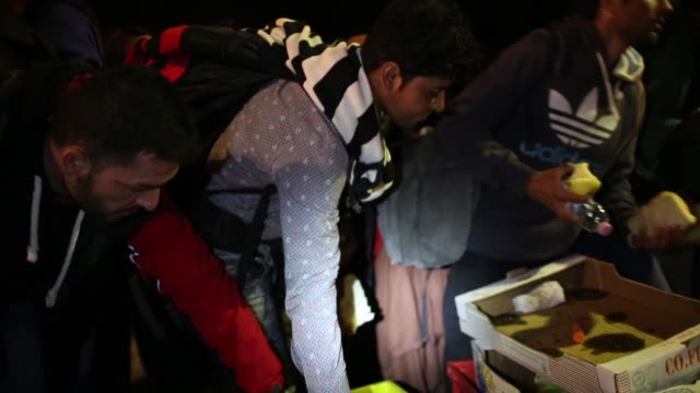 Migrants who arrived on the third train today at Hegyeshalom on the Hungarian and Austrian border are given food by volunteers as they walk the four...
