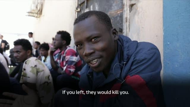 african migrants stuck in migrant camp in libya tell of the efforts to reach europe libya tripoli al nasr migrant camp ext various of migrants stand... - ラゲ オマール点の映像素材/bロール