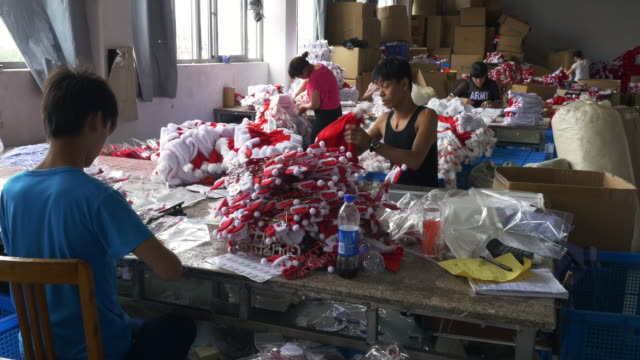 migratory chinese workers create cheap christmas decorations hats and gifts for european export from the city and factories of yiwu - large group of objects stock videos and b-roll footage