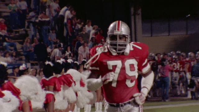 1985 MS TS Mike Clark of Tampa Bay Bandits entering field between rows of cheerleaders/ Clark high-fiving teammates/ Tampa, Florida