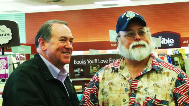 Mike Huckabee signs fans' copies of his new book 'God Guns Grits and Gravy'