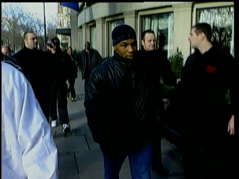 mike tyson walking along park lane in london surrounded by bodyguards / he shakes the hands of some fans / mike puts hand up to block paparazzi... - mike tyson boxer stock videos and b-roll footage