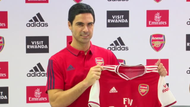 mikel arteta new manager of arsenal football club walks into press conference and photo op of him holding up arsenal shirt - sportswear stock videos & royalty-free footage