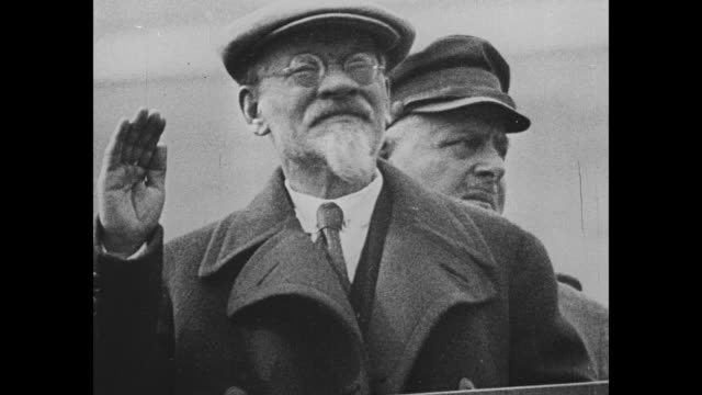 vídeos de stock e filmes b-roll de mikhail kalinin, chairman of the central executive committee of the all russian congress of soviets, stands on the tribune of lenin's mausoleum, with... - dia do trabalhador
